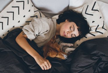 woman sleeping with a dog by her side