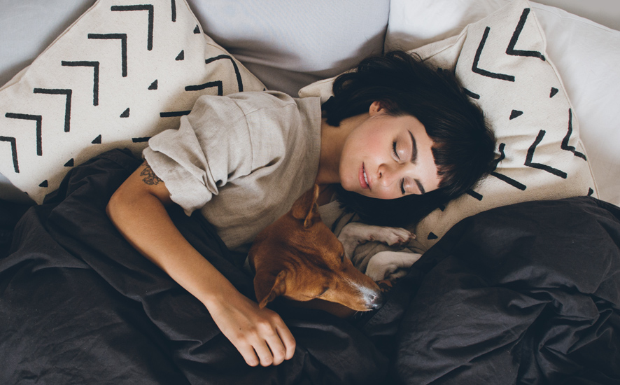 lady sleeping with a dog in her bed