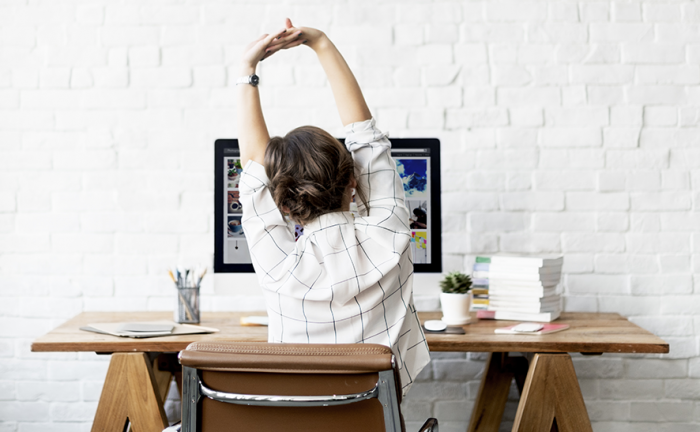 a woman sitting in front of a desk stretching her arms up