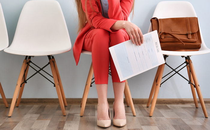 woman in a red suit sitting in a waiting room with a resume in her hand