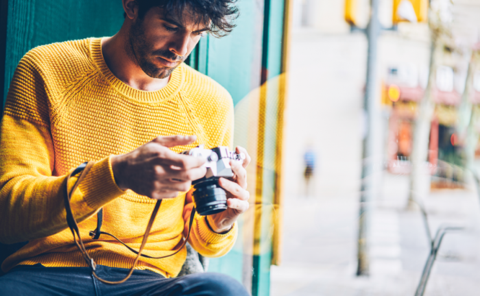 man in a yellow sweater with a camera