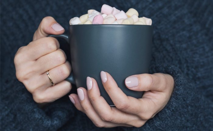 woman holding a cup with marshmallows