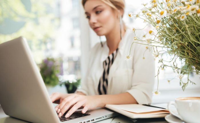 lady sitting in fron of a laptop next to flowers